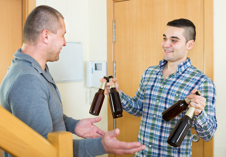 buddy: Guy meeting smiling buddy with alcoholic bottles at doorway Stock Photo