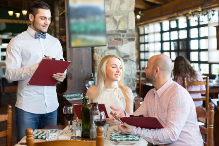 camarero: Camarero masculino joven alegre que servir a los clientes del restaurante en la mesa. Enfoque selectivo