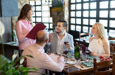 respectful: Portrait of smiling  people having dinner and respectful waiter Stock Photo