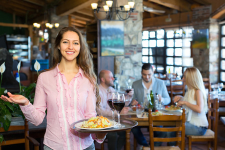 respectful: Portrait of happy adults having dinner and respectful waiter