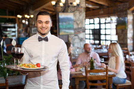 respectful: Adults people having dinner and respectful waiter
