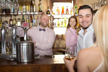 entertaining: Positive bartender entertaining guests at bar counter