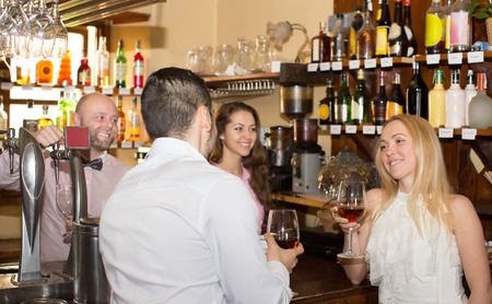 entertaining: Happy bartender entertaining guests at bar counter