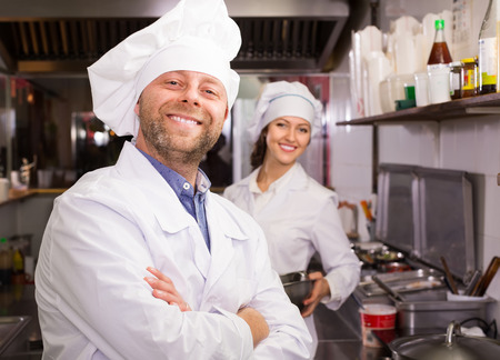 food service occupation: Portrait of hospitable smiling chef and his helper at bistro kitchen