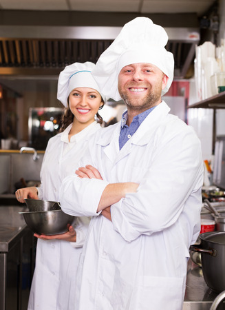 bistro: Hospitable happy cooks greeting customers at bistro kitchen and smiling Stock Photo