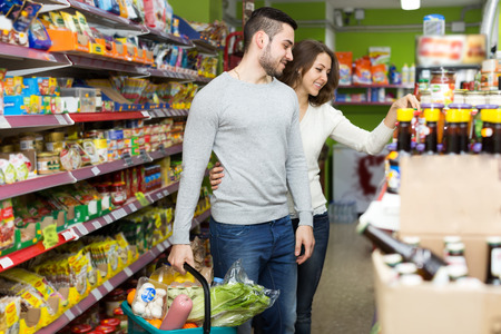food store: Couple of positive young adults choosing canned food in a shop