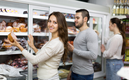happy client: Happy customers standing near fridge with meat products Stock Photo