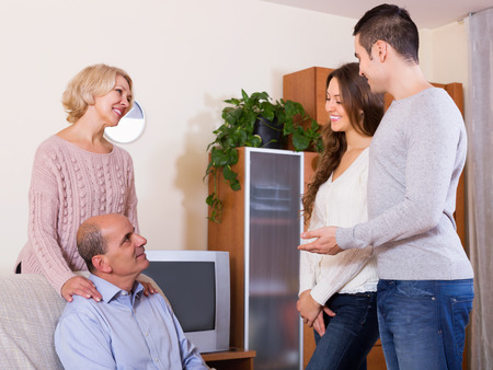 affiance: Happy young man showing his future wife to smiling parents in living room