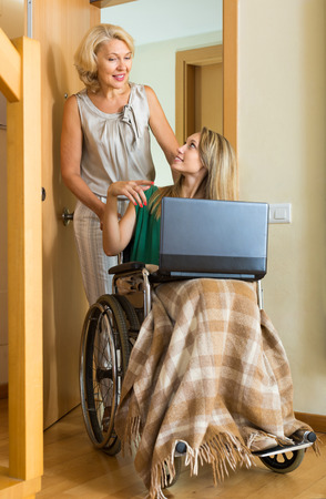 incapacitated: Friendly adult social worker and disabled woman on chair with laptop Stock Photo