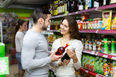 Smiling couple with bottles of wine in their hands are choosing wine in a supermarket photo