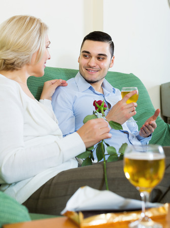 Mature woman chatting with young boyfriend indoors