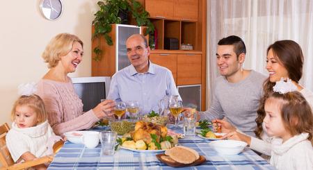 Familiar positiva multigeneracional almorzando juntos en la habitación