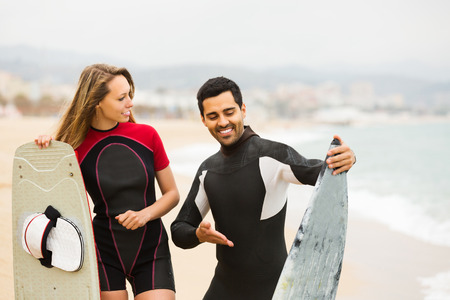 surfers: Surfers family on the beach in wetsuits