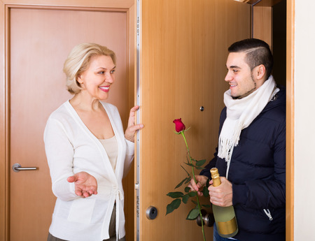 liaison: Aged smiling woman meeting young boyfriend with flowers and wine in hands at doorway