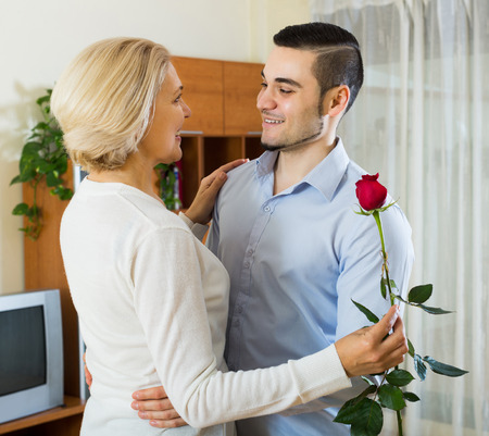 mismatch: Adult son asking senior mother to dance at home Stock Photo