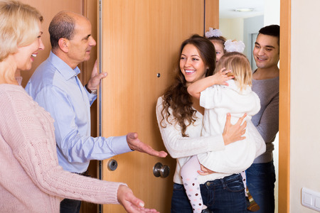visits: Happy aged couple meeting kids and grand children at doorstep Stock Photo