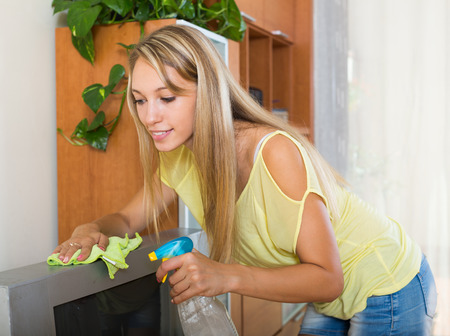 televisor: Smiling young woman  wiping the dust on TV in living room at home Stock Photo