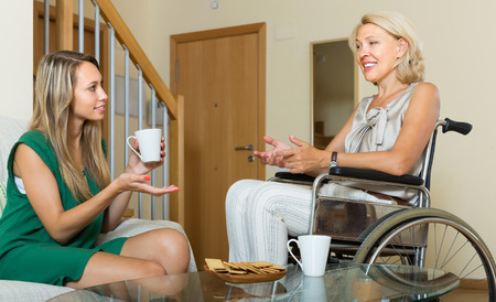incapacitated: Happy women in wheelchair and girl drinking tea at home. Focus on young