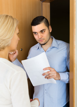 Male agent trying to collect money from aged blonde housewife at home door Stock Photo