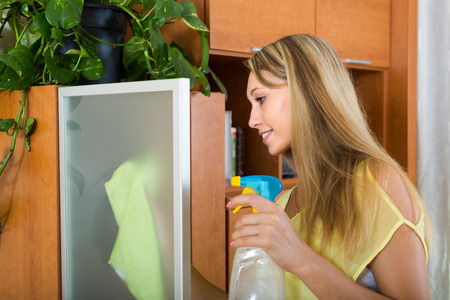 dusting: Young woman dusting glass of furniture at home