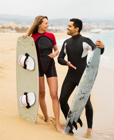 surfers: Young surfers couple on the beach in wetsuits