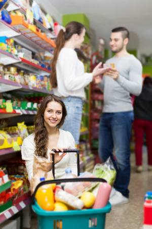 canned goods: Positive customers standing near shelves with canned goods at shop