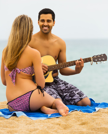 serenading: Happy adult family resting on the shore with a guitar