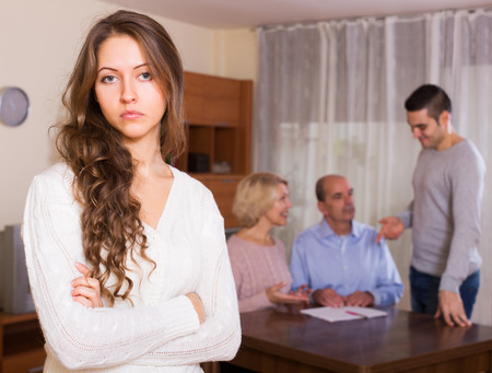 misunderstanding: Unhappy long-haired woman fased with misunderstanding family Stock Photo
