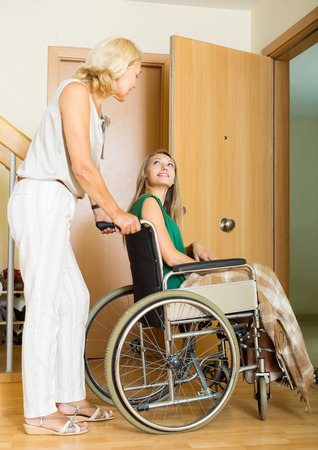 incapacitated: Happy women in wheelchair with female assistant at threshold