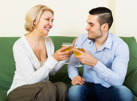 mismatch: Happy mature woman chatting with young boyfriend indoors
