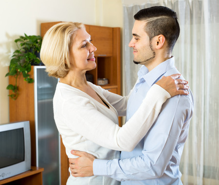 gigolo: Cheerful mature woman and young boyfriend dancing indoors Stock Photo