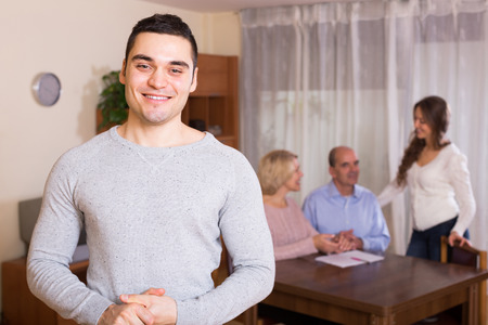 hypothec: Happy adult smiling man staying near united family members