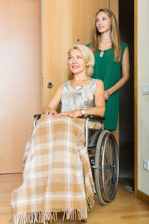threshold: Smiling old woman in wheelchair with young assistant at threshold