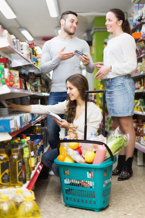 canned goods: Cheerful adults people standing near shelves with canned goods at shop Stock Photo