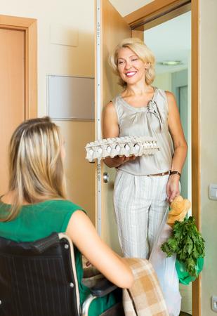 doorstep: Happy woman in wheelchair meeting assistant with bags at doorstep