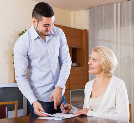 Happy mature woman and young fiance signing marriage settlement Stock Photo