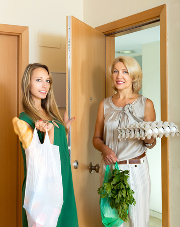 after shopping: Two female friends returnind home after  shopping with food