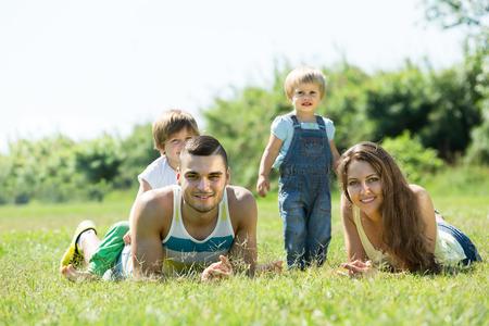2 to 3 years: Ritratto di famiglia felice di quattro sdraiato sul prato in soleggiata estate parco Archivio Fotografico