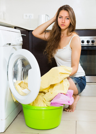 unsound: Home laundry. Sad young housewife with clothes near washing machine at home