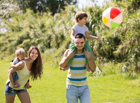 Smiling young parents with little daughters playing with ball outdoor photo