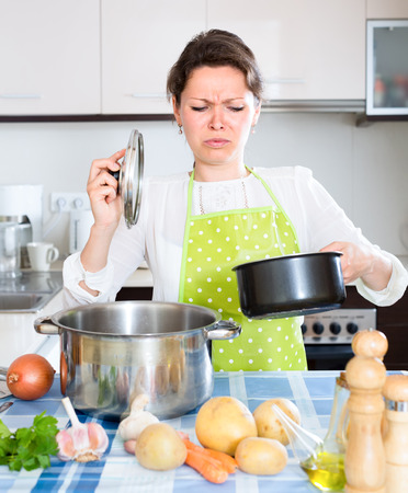foul: Young woman in kitchen opened a pan with smelly foul food inside