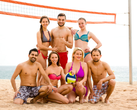 Group portrait of volleyball players on a sandy summer beach near sea or ocean photo