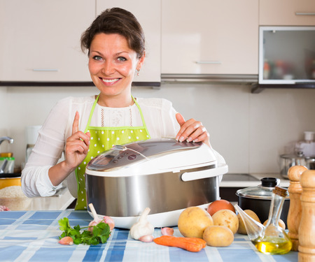 Smiling  woman using slo-cooker at home Stock Photo