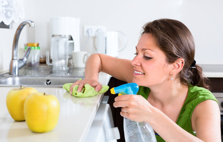 doing chores: Beautiful woman doing chores around the house thoroughly cleaning furtniture in kitchen