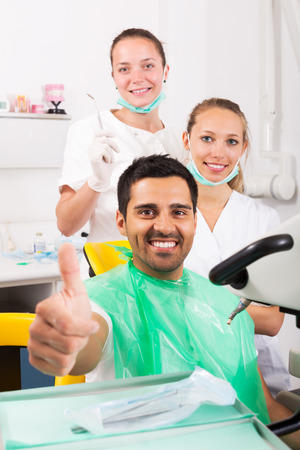 trained nurse: Happy male patient satisfied with the work of the dentist. Focus on  the man