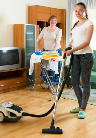 clean home: Young daughter with senior mother clean at home together