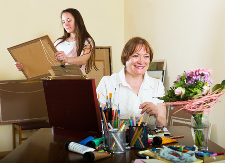 the admirer: Girl buyer select picture of woman artist at studio Stock Photo