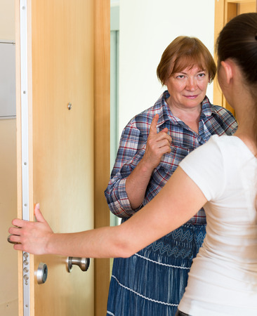 welcom: Senior aggressive woman have conflict with neighbour at the doorway Stock Photo
