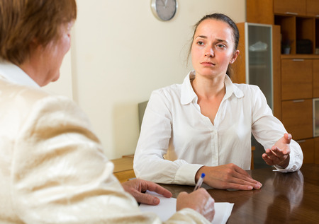 serious meeting: Mature lady and a young woman having a serious meeting at desk in the office Stock Photo