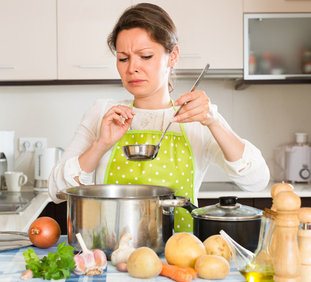 unskilled: Young housewife feeling bad smell from pan at the home kitchen Stock Photo